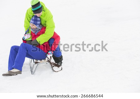 Young man embracing woman on sled in snow - stock photo