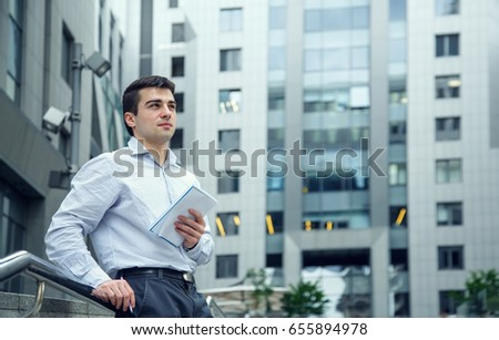 Young man employee on the background of an office building. Go out on break, that would think and make notes of fresh ideas.