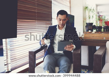 Young man employer with cup of coffee in hand is reading resumes on portable touch pad before interview with specialists. Successful business worker is reading news on web site via digital tablet - stock photo