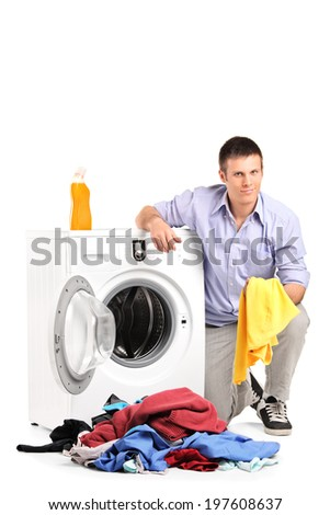 Young man emptying a washing machine isolated on white background