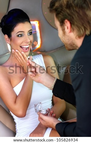 Young man engaging surprised beautiful woman with engagement ring. - stock photo