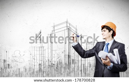 Young man engineer in helmet drawing construction project - stock photo