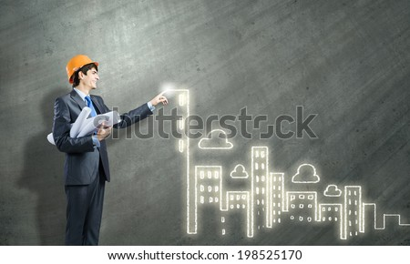 Young man engineer touching icon of media screen - stock photo