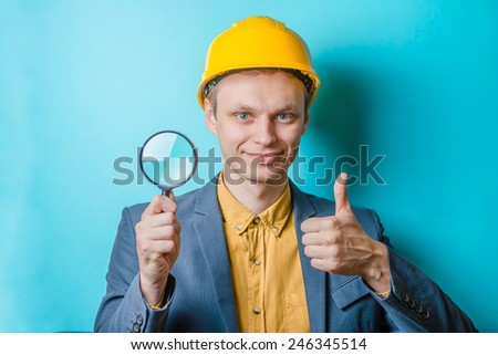 Young man engineer with magnifier - stock photo