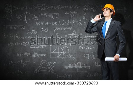 Young man engineer with project in hands talking on mobile phone and sketches on wall - stock photo