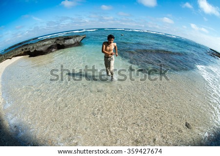 Young man enjoy in transparent beach in Ly Son island, Quang Ngai, Vietnam. Traveler explore the beach.