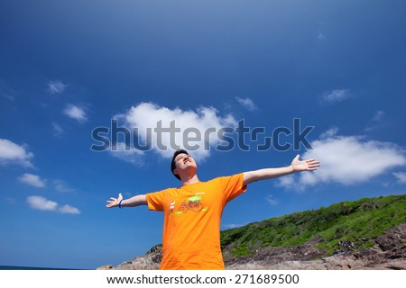 Young man enjoy over the blue sky - stock photo