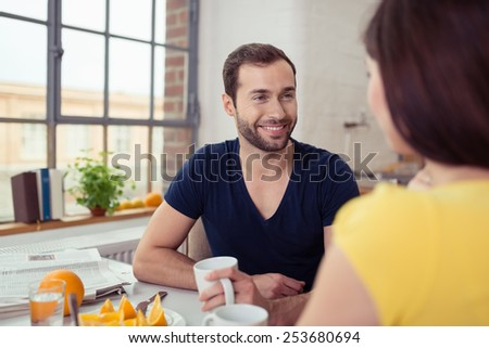 Young man enjoying a healthy breakfast with his wife sitting at the table smiling and chatting with coffee in his hand, view over her shoulder - stock photo
