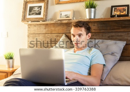 Young man enjoying a laptop computer while lying on the bed. Home interior. - stock photo