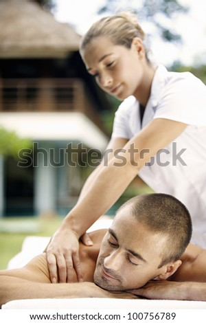 Young man enjoying a massage in a spa, outdoors.