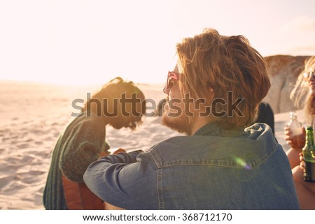 Young man enjoying a summer day at the beach with group of friends in background. Young people enjoying a day on the beach. - stock photo