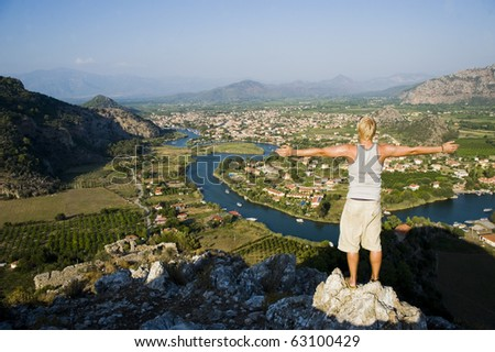 Young man enjoying his freedom at the top of a mountain - stock photo