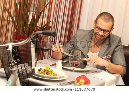 young man enjoying meal with a a bike - stock photo