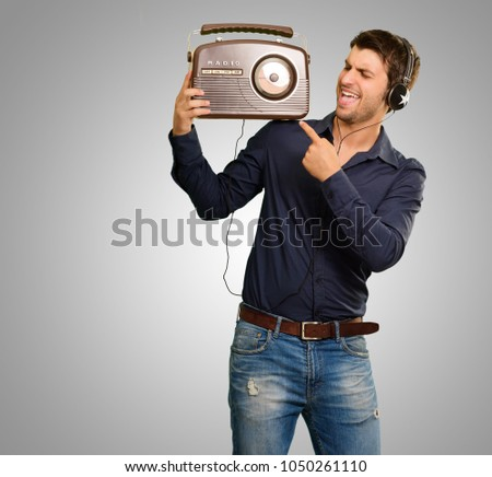 Young Man Enjoying Music On Grey Background