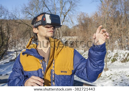 Young Man enjoying virtual reality glasses in the park, Prague, Czech republic, 8th of January, 2016