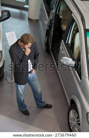 Young man examining new car at showroom - stock photo