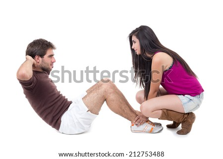 Young man excercising with beautiful female personal trainer doing situpsisolated on white - stock photo