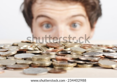 Young man excited with pile of UK money - stock photo
