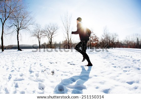 Young man exercise running on snow during sunny winter day - stock photo
