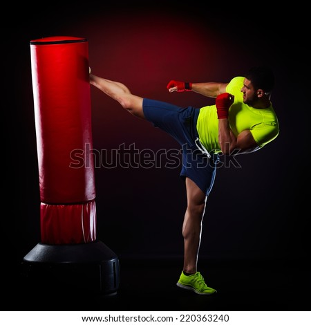 young man exercising bag boxing in studio - stock photo