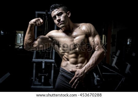 Young man exercising in dark and old gym - stock photo