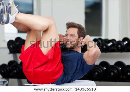 Young man exercising in gym - stock photo