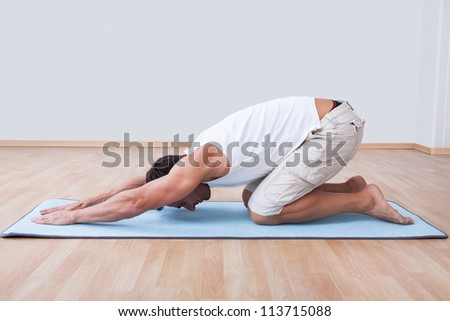 Young Man Exercising On Exercise Mat, Indoors - stock photo