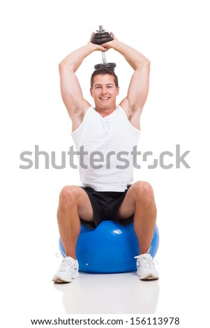 young man exercising with dumbbells on a fitness ball on white background - stock photo