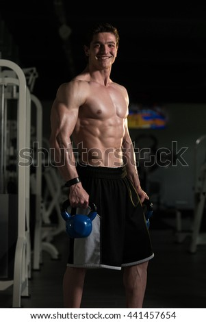 Young Man Exercising With Kettle Bell And Flexing Muscles - Muscular Athletic Bodybuilder Fitness Model Exercises - stock photo