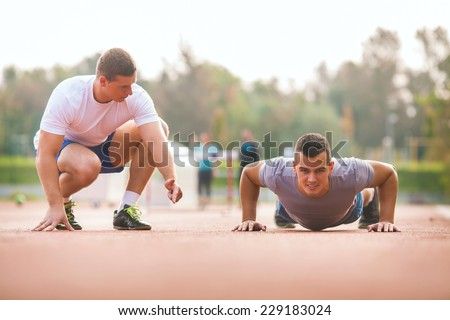 Young man exercising with personal trainer - stock photo
