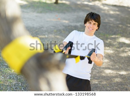 Young Man Exercising With Stretch Band; Outdoors - stock photo