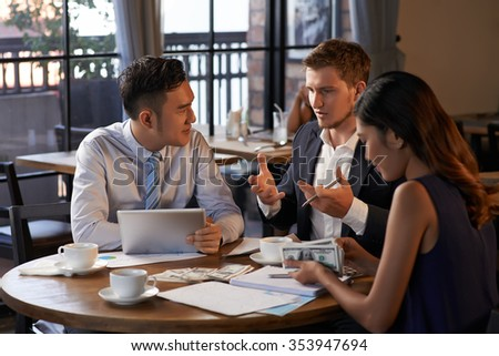 Young man explaining business idea to coworkers, when they are sitting in cafe - stock photo