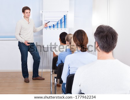 Young Man Explaining Graph To His Colleagues Sitting On Chair - stock photo