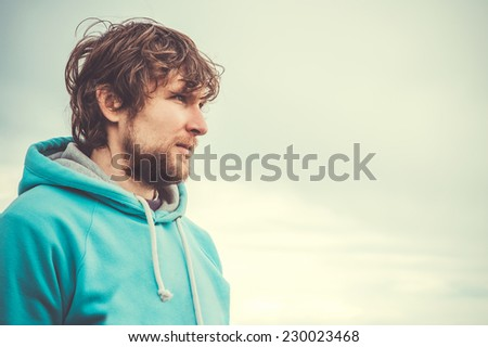 Young Man Face Portrait Beard and curly hair Outdoor Lifestyle Urban Fashion Travel concept - stock photo