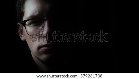 Young man face portrait in low key - stock photo