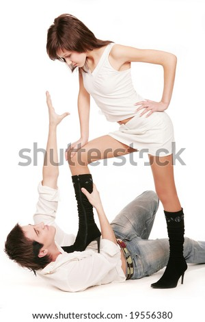 Young man falling on white background and girl standing by her foot on his chest