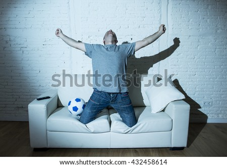 young man fanatic and crazy football fan watching television soccer match alone screaming happy celebrating scoring goal in glad in ecstasy with ball on home couch - stock photo