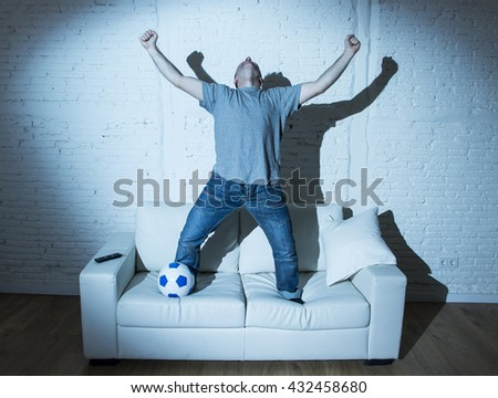young man fanatic and crazy football fan watching television soccer match with ball jumping on sofa couch screaming happy celebrating goal in ecstasy