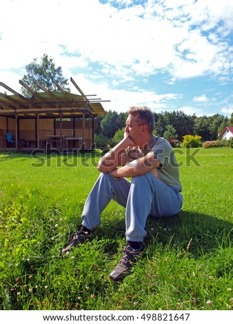 Young man farmer is sitting on grass with closed eyes and thinking.