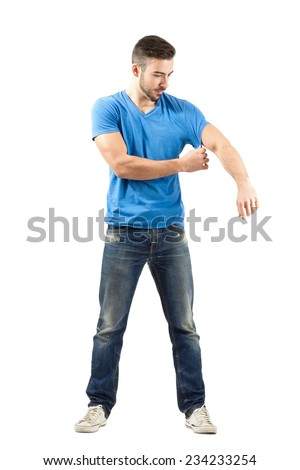 Young man fashion model taking off his shirt while holding sleeve. Full body length portrait isolated over white background. - stock photo