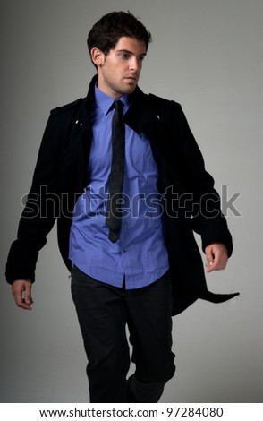 Young man fashion with suit walking over grey background
