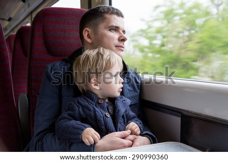 Young man - father, travelling with his little son by train, looking at the window. - stock photo