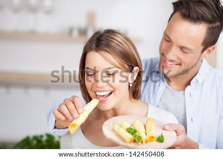 Young man feeds a piece of cheese at his girlfriend - stock photo