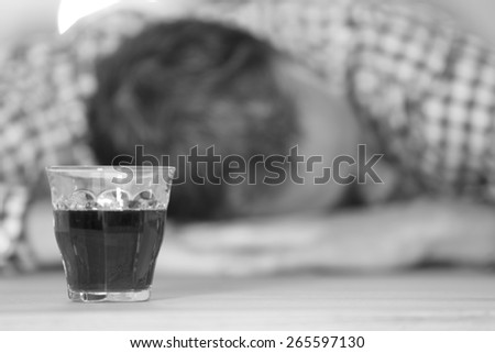 Young man feeling alone and drinking too much alcohol in his own home at the table - stock photo