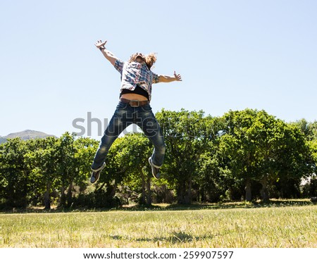 Young man feeling free in the park on a summers day