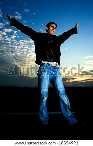 young man feels the freedom on top of the roof - stock photo