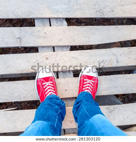 young man feet in red sneakers on road - stock photo