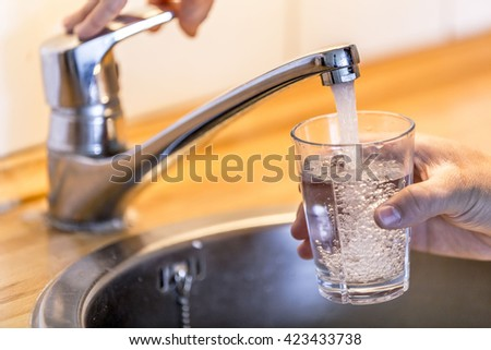 Young man filling up a glass with water in the sink in kitchen at home.