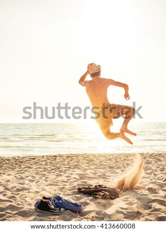 Young man finally at the beach jumping of happiness - stock photo