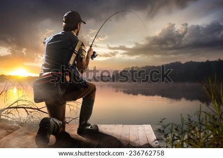 Young man fishing at misty sunrise  - stock photo